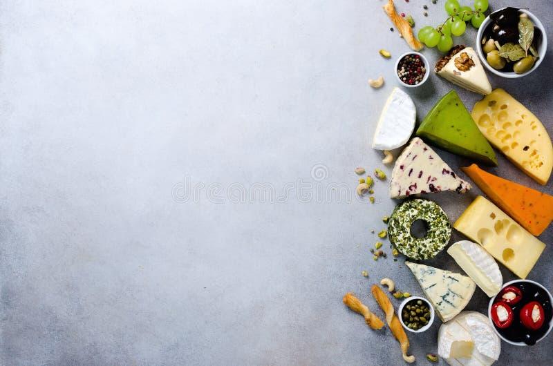 分类艰苦,不很软和软干酪用橄榄, grissini面包条,雀跃,葡萄,在灰色混凝土 免版税图库摄影