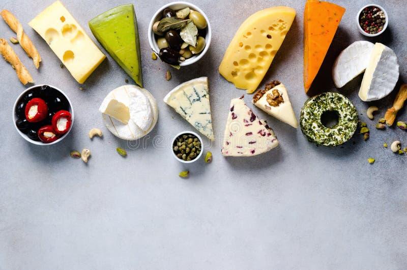 分类艰苦,不很软和软干酪用橄榄, grissini面包条,雀跃,葡萄,在灰色混凝土 库存照片