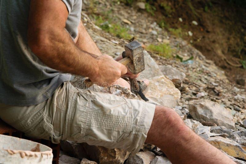 分裂与锤子和凿子的岩石工匠的细节 免版税库存照片