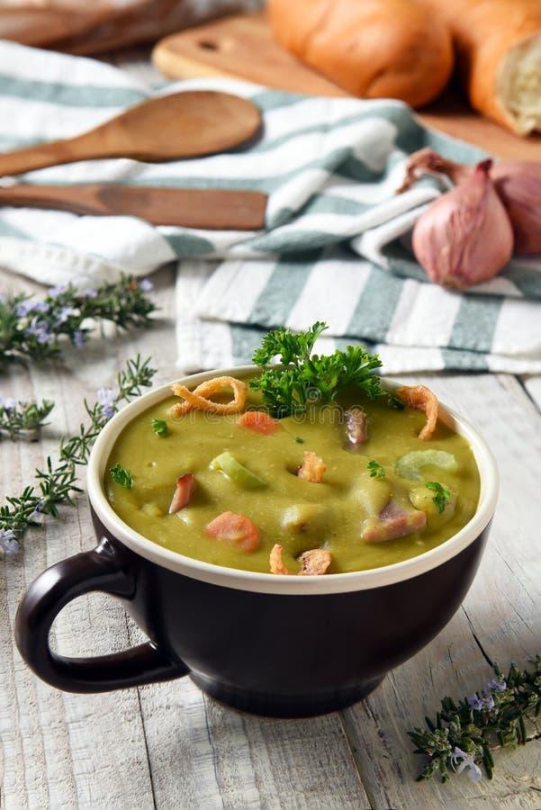 分裂在一个杯子的浓豌豆汤在白色土气厨房用桌上 库存照片