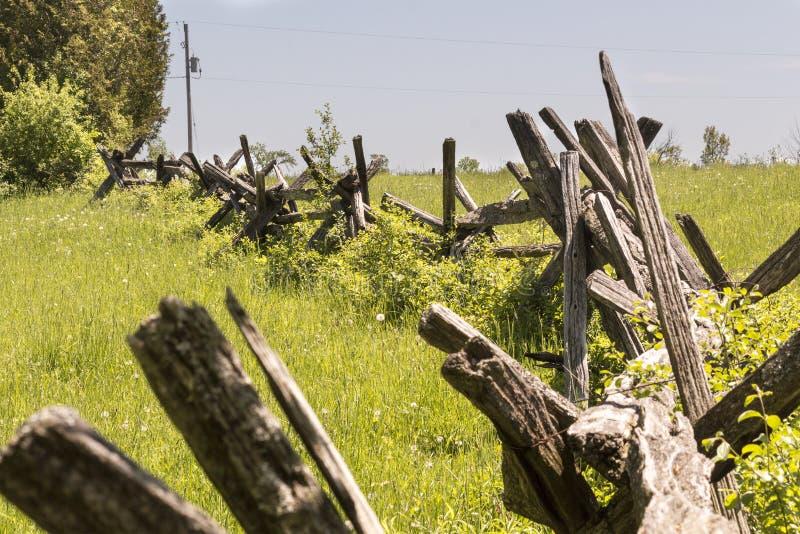 分裂雪松栅栏通过在一个农村社区的领域弯曲农场的 免版税库存图片