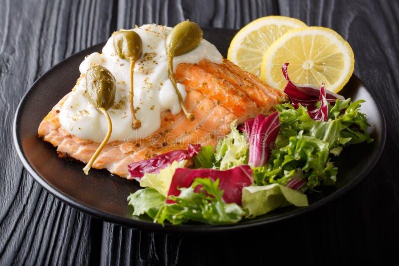 分配烤三文鱼用奶油沙司、雀跃,柠檬和新鲜 免版税库存图片