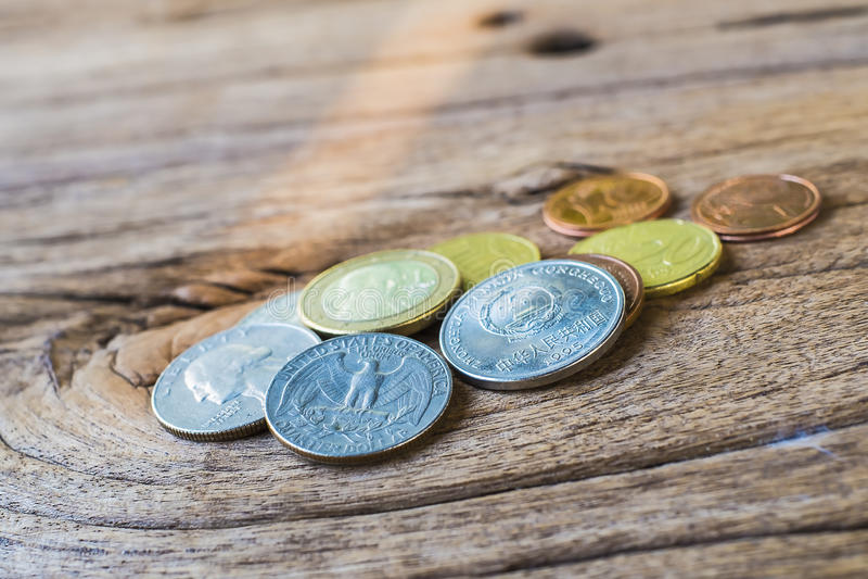 分类在老粗砺的布朗木头的硬币 免版税库存照片
