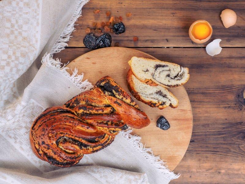切与罂粟种子的甜扭转的小圆面包 在土气样式,例证的静物画早餐,菜单的盖子 顶视图 免版税库存照片