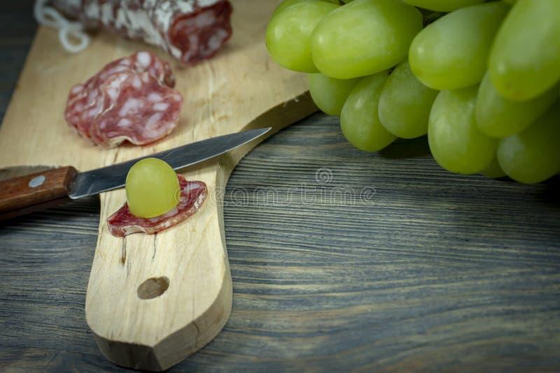 切了在切片Fuet香肠的新鲜的绿色葡萄 免版税库存图片