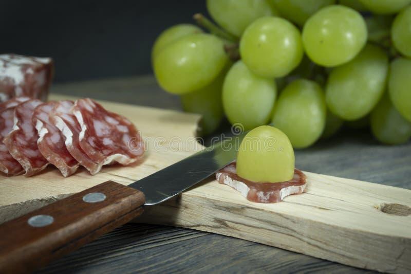 切了在切片Fuet香肠的新鲜的绿色葡萄 库存图片