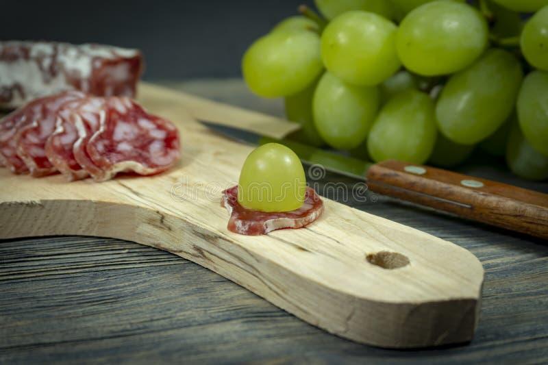 切了在蒜味咸腊肠的新鲜的绿色葡萄 免版税库存图片