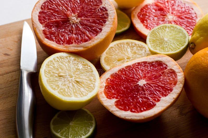 切了新鲜的柑橘柠檬,石灰,在一个木板有金属刀子的,侧视图的葡萄柚 库存照片