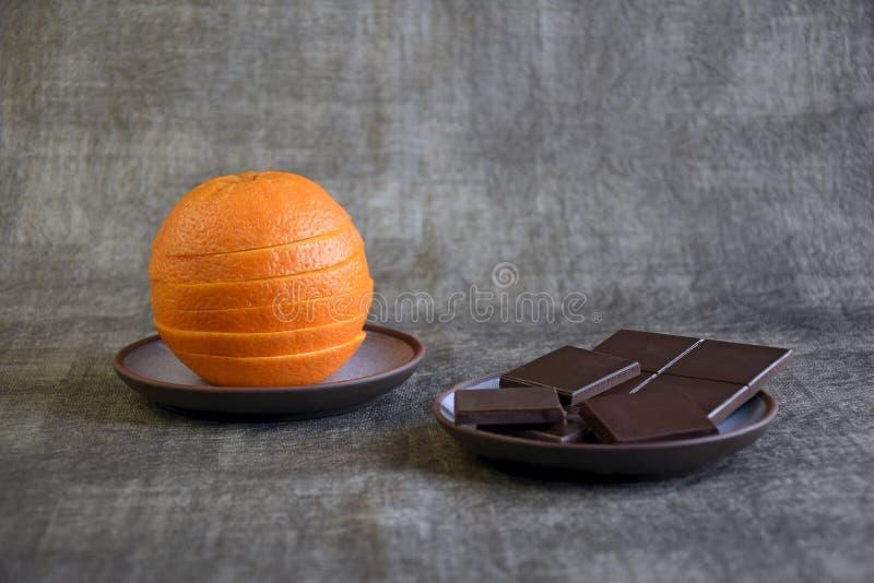 切了新鲜的桔子和黑暗的巧克力 免版税库存图片