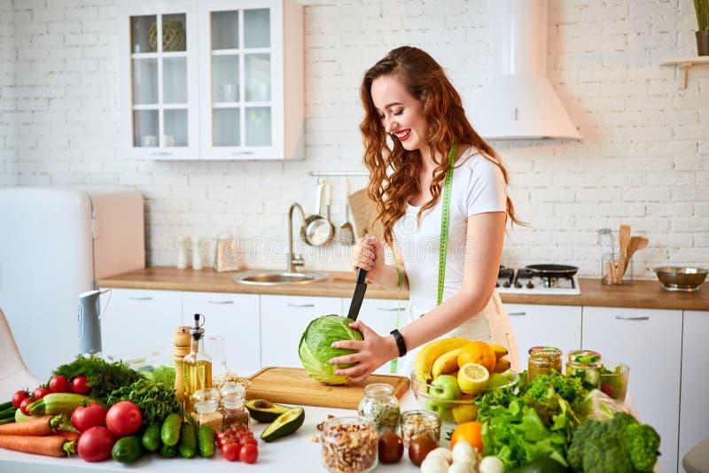 切做的年轻愉快的妇女沙拉圆白菜在有绿色新鲜的成份的美丽的厨房里户内 健康食品和 库存照片