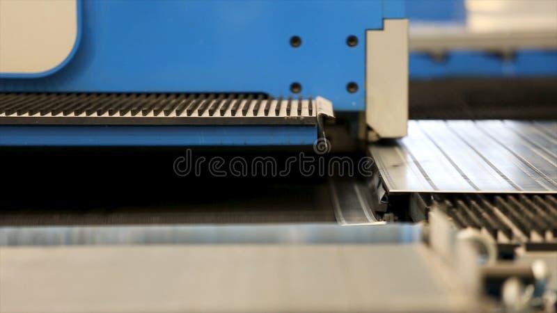 切口钻孔穿孔盖印金属板在工业CNC机器 CNC同等猛击的特写镜头射击 免版税图库摄影