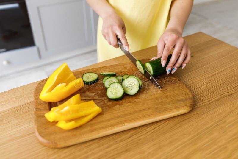 切在一个木板的年轻女人新鲜蔬菜沙拉的 ?? 女孩切一个黄瓜,特写镜头 免版税库存图片