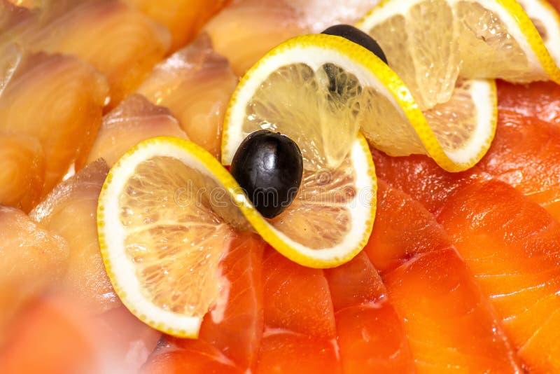 切在一块板材的另外红色和白色鱼用橄榄和柠檬在板材 库存图片