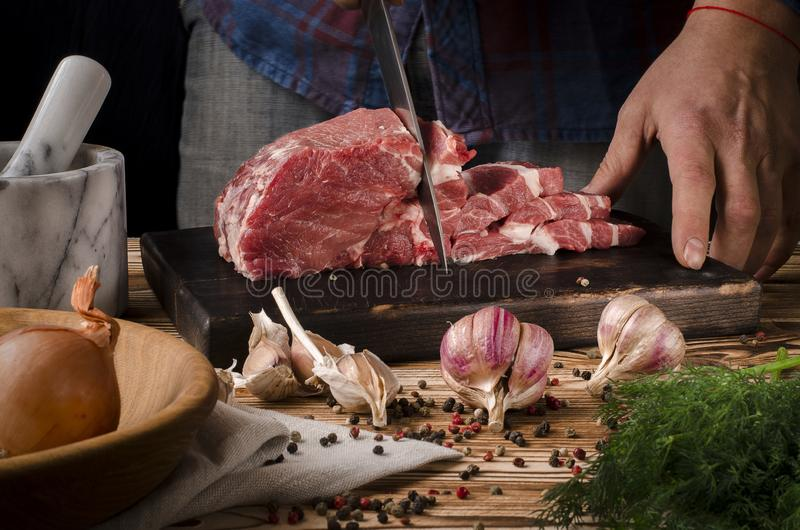 切在木板的屠户猪肉在黑暗的背景的一张木桌上 免版税库存图片