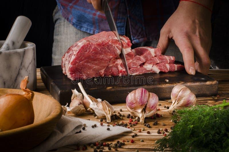 切在木板的屠户猪肉在黑暗的背景的一张木桌上 库存图片