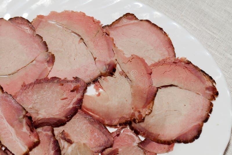 切在白色板材的熏制的肉 库存照片