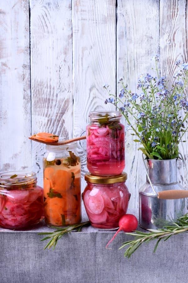 切好的在玻璃瓶子和红洋葱用卤汁泡的萝卜、红萝卜 免版税库存图片