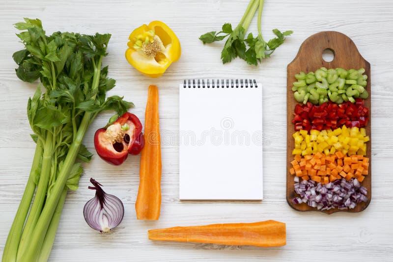 切好的新鲜蔬菜在切板和空白的笔记薄安排了在白色木桌,顶上的看法 平的位置,从上面 免版税图库摄影