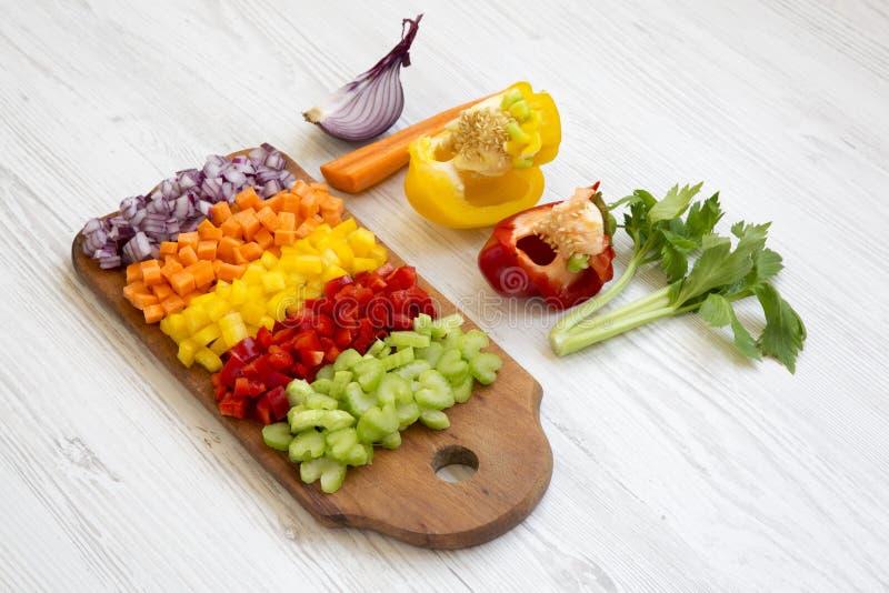 切好的新鲜蔬菜在白色木表面,侧视图上的切板安排了 库存图片