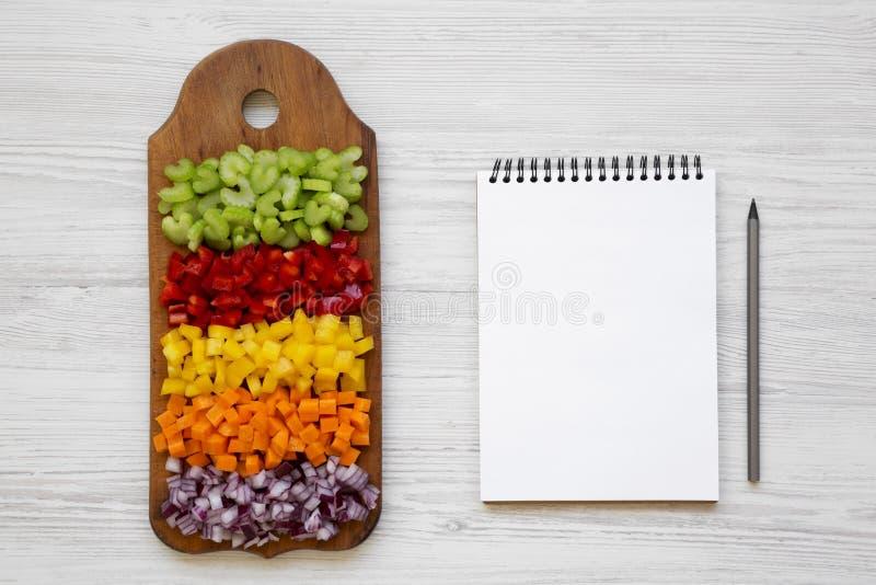 切好的新鲜蔬菜红萝卜,芹菜,红洋葱,色的胡椒在切板,在一白色木的空白的笔记薄安排了 库存图片
