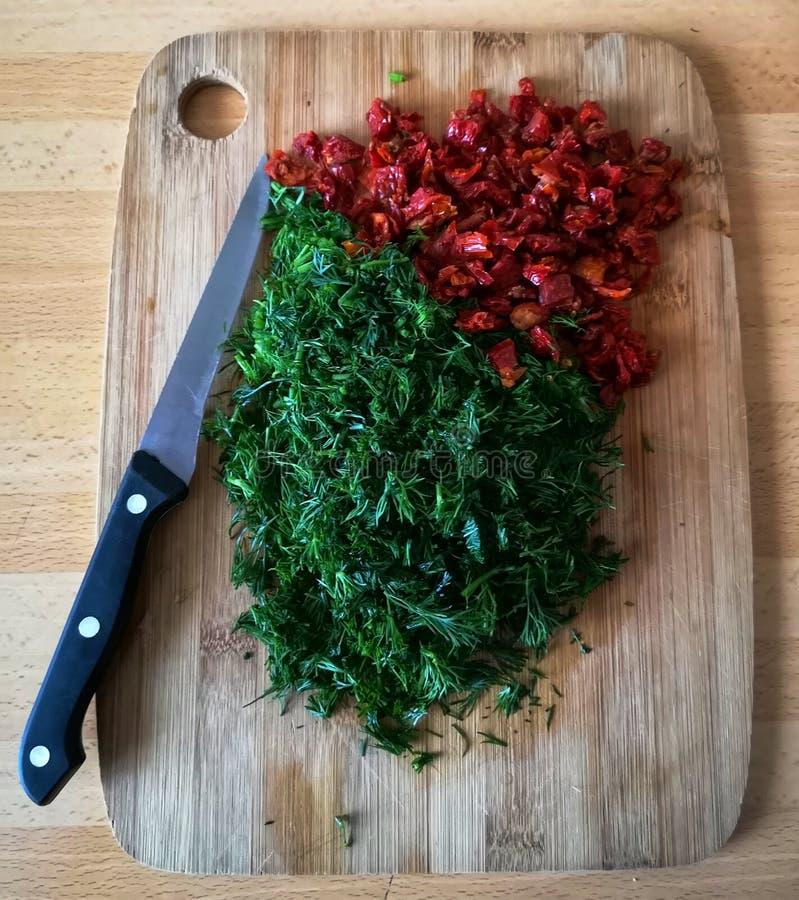 切好的莳萝和干蕃茄 库存照片