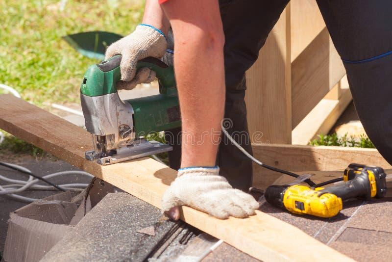 切开一块木头的木工使用竖锯 图库摄影