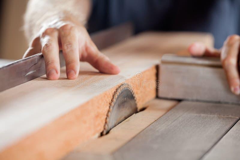 切开与Tablesaw的木匠的手木头 免版税库存照片