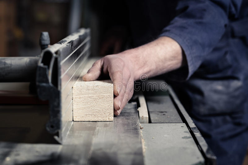 切开与Tablesaw的木匠的手木头 免版税库存图片