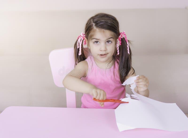 切开单独纸与剪刀的逗人喜爱的女孩画象 库存图片