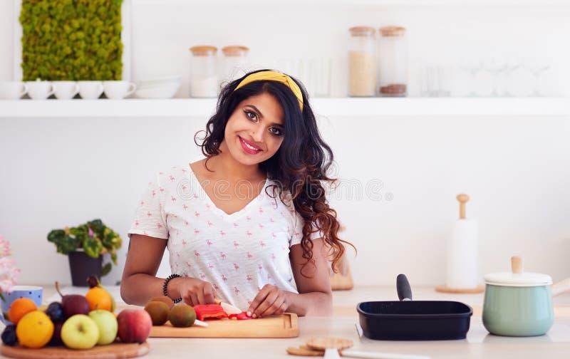切开在厨房,健康吃的美丽的愉快的年轻印度妇女菜 免版税图库摄影