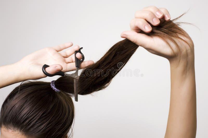 切开她的马尾辫的妇女 免版税库存图片