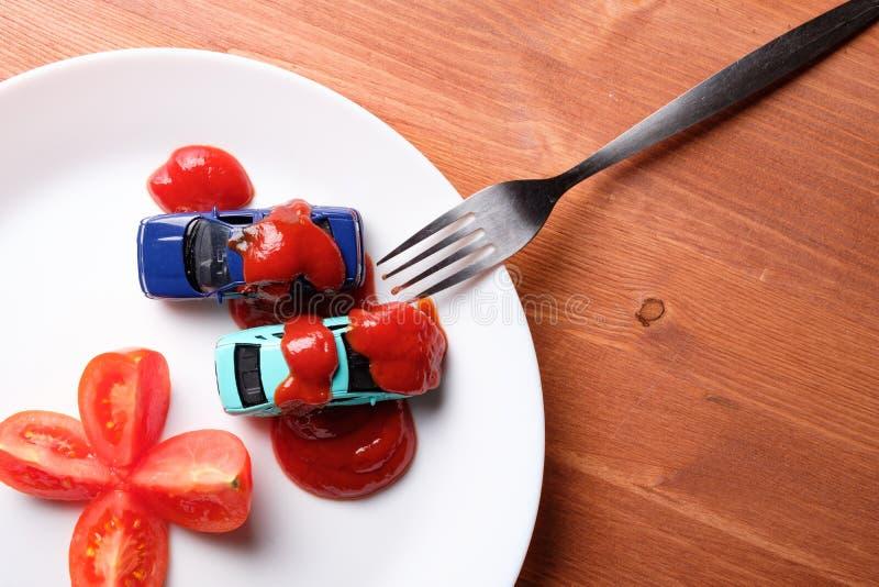 切开成蕃茄在它旁边是用番茄酱层数盖的两辆汽车的四部分,它所有在一块白色板材 库存照片