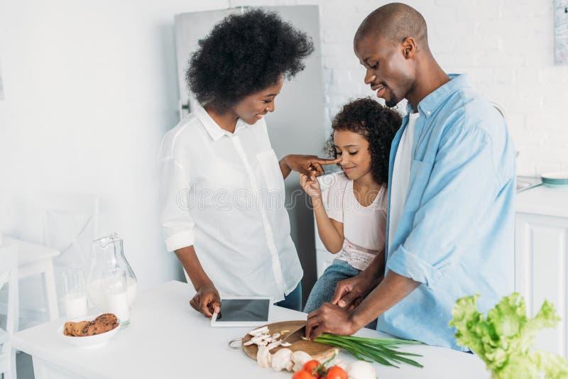 切开新鲜蔬菜与站立近在厨房里的家庭的早餐的非裔美国人的人 库存图片