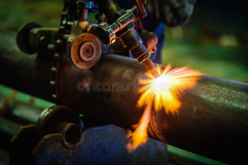 切开有乙炔焊切割吹管的a的工作者钢管 免版税库存图片