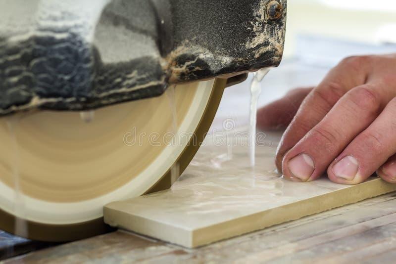 切开有水切割机clos的工作者手陶瓷砖 库存图片