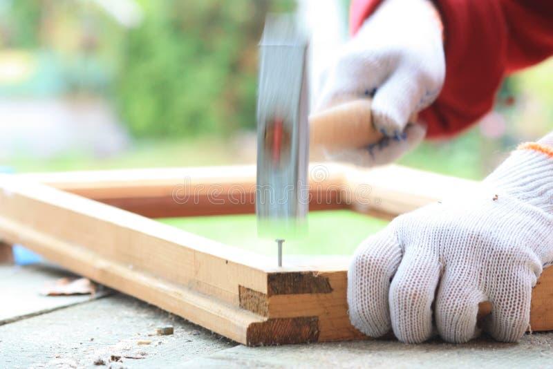 切开木材用sawHammering钉子的手入与锤子的一个木制框架 库存照片
