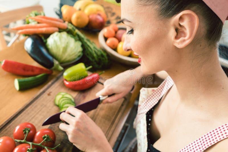 切开沙拉的葡萄酒主妇菜在她的厨房里 库存图片