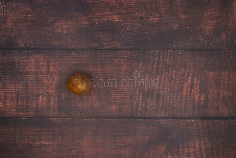切开猕猴桃在木背景的机智刀子 库存照片