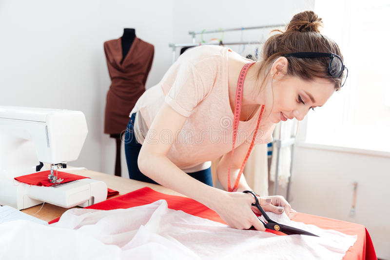 切开白色织品的被聚焦的妇女时装设计师在演播室 图库摄影