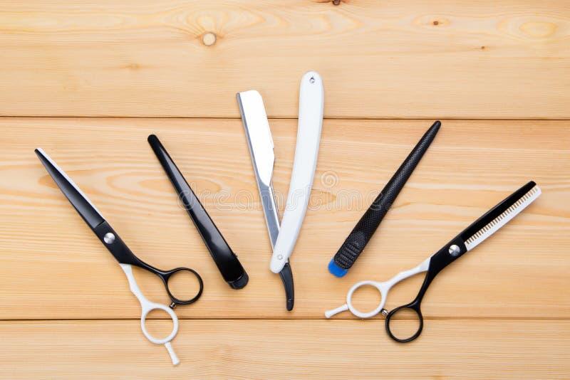 切开的头发和胡子对象,剃刀和剪刀,梳子,在轻的木背景的谎言 库存图片