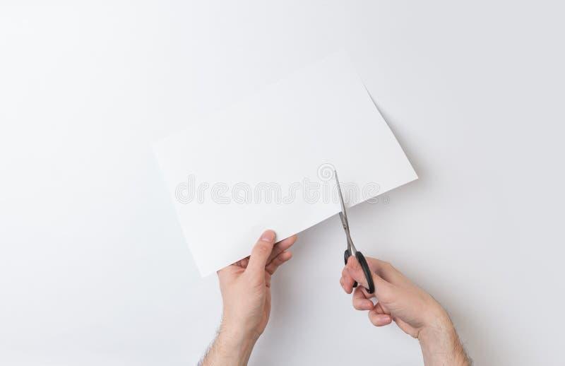切开纸的两只手 图库摄影