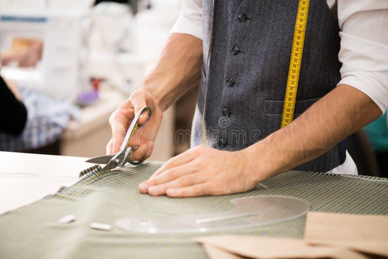 切开织品的男性裁缝 免版税库存照片