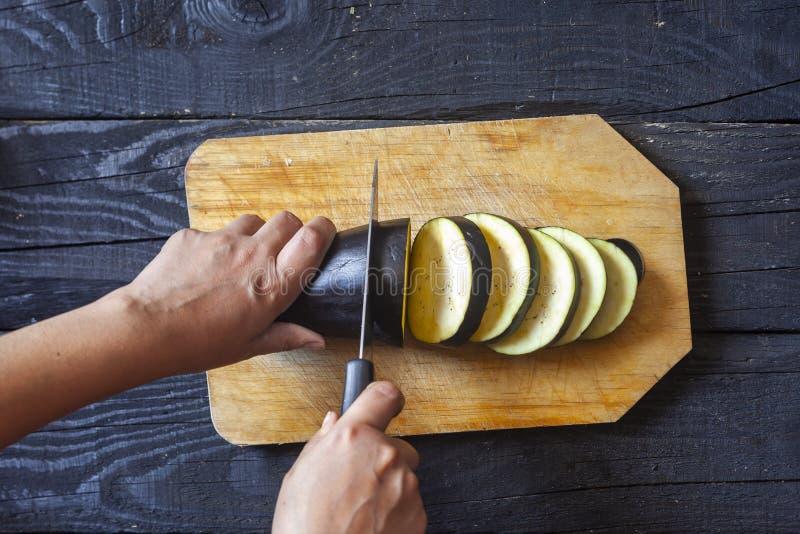 切开菜的手在厨房里 女性切大茄子 库存照片