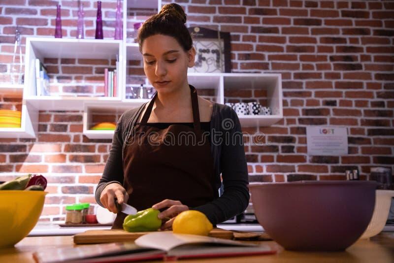 切开菜的有吸引力的女性模型在厨房里 免版税图库摄影