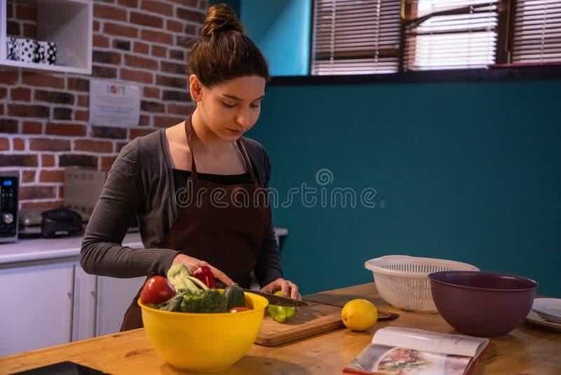 切开菜的有吸引力的女性模型在厨房里 图库摄影