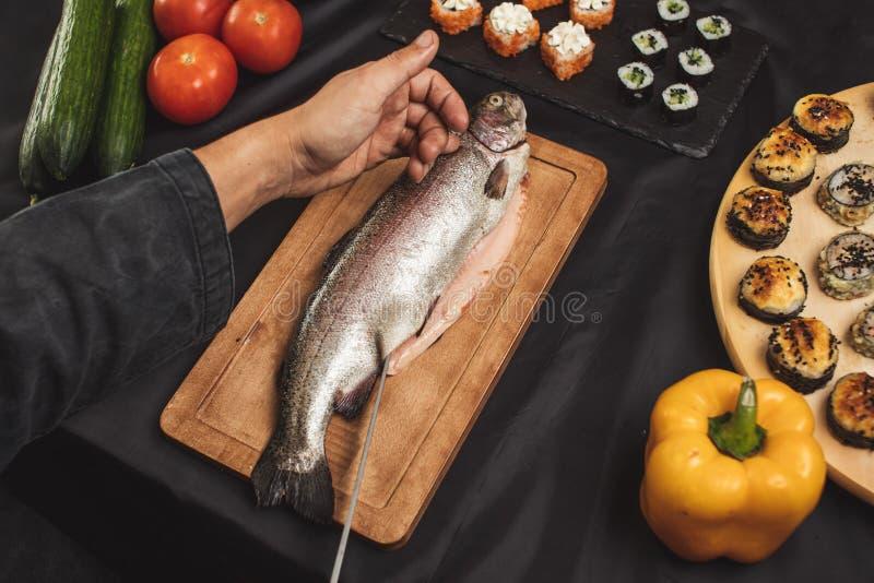 切开鱼片的人的手在餐馆 免版税库存照片