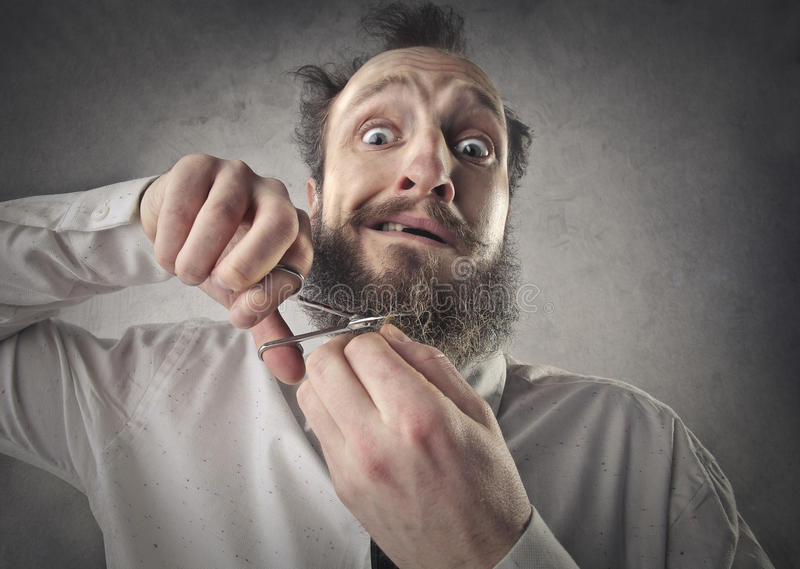 切开他的胡子的人 免版税库存图片