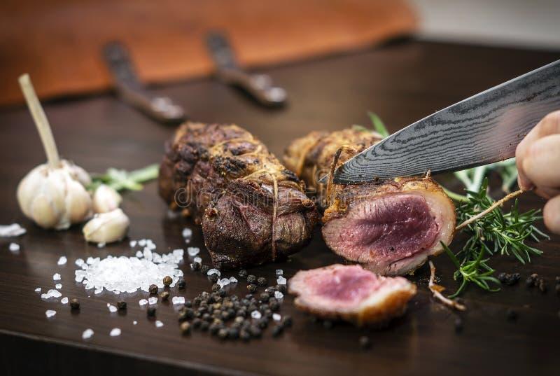 切有机烤牛肉滚动在与成份的木桌 免版税图库摄影