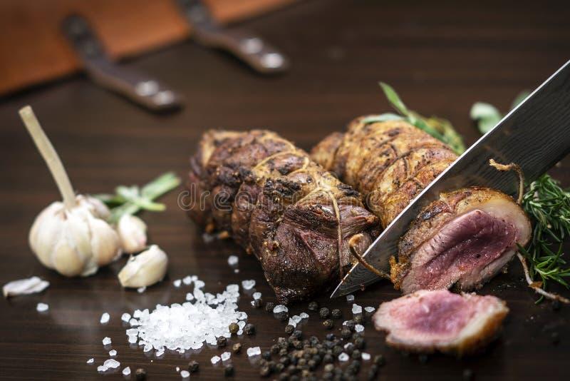 切有机烤牛肉滚动在与成份的木桌 免版税库存照片
