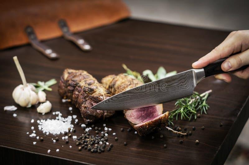 切有机烤牛肉滚动在与成份的木桌 免版税库存图片